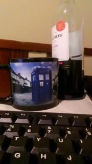 Writing while drinking wine from a Tardis mug.